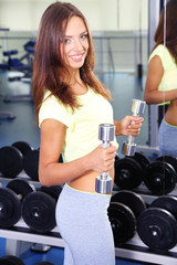 Pretty sporty girl with dumbbells in gum