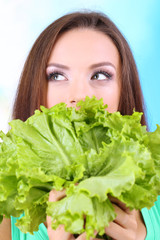 Beautiful girl with fresh salad on blue background