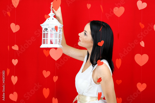 Attractive young woman with lantern on Valentine Day