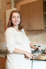 pregnant woman cooks salmon