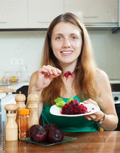 Casual  girl in green eating boiled beets