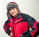latin man wearing aftificial fur hat with ear flaps indoor