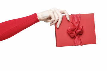 Hand holding red present box with big bow isolated on white back