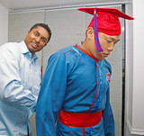 professor helping  student  to wear graduation gowns