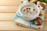 Mushroom soup in pot, on color napkin,  on wooden background