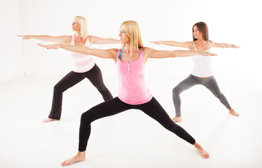 Three beautiful women doing Yoga Warrior II Pose.