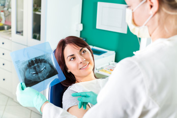 Dentist showing to the patient X-ray picture