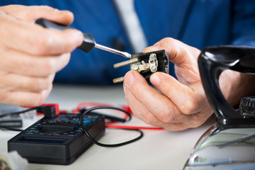 Electrician checking and repairing old power plug