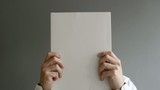 Businessman holding blank paper in front of his face with copy s