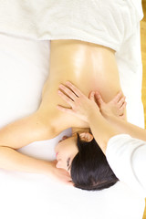 Therapist doing strong back massage to relaxed woman in spa