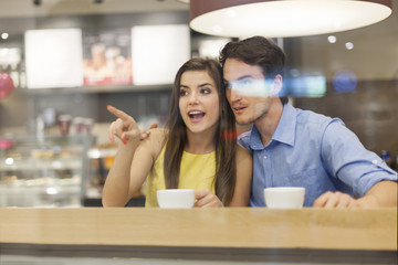 Shocked couple looking through window from cafe