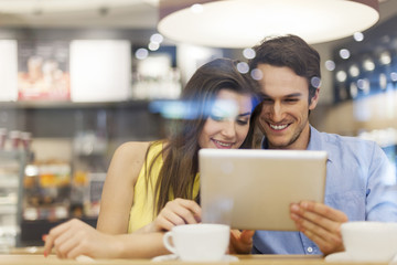 Couple in cafe with digital tablet