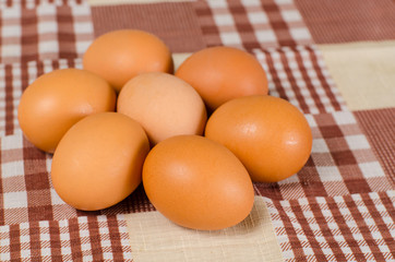 raw eggs on the squared tablecloth
