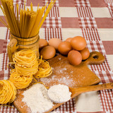 raw eggs, spaghetti, meal on the squared tablecloth