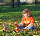 beautiful little girl and teddy bear in park
