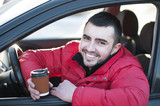 Attractive man in his  car drinking coffee outdoors.