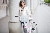 Young woman using mobile phone standing by her bicycle
