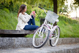 Young woman sitting on the bench next to her bike and texting. U