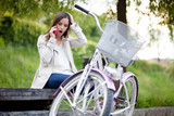 Young woman sitting on the bench next to her bike talking on the