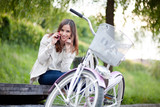 Young woman sitting on the bench next to her bike and talking on