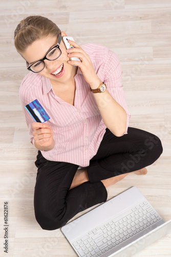 Online shopper sitting with laptop and paying by credit card