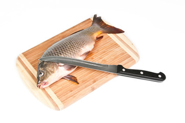 Fresh fish on the cutting board with knife