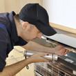 Handwerker repariert defekten Herd