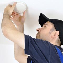 Handwerker montiert Rauchmelder als Feueralarm