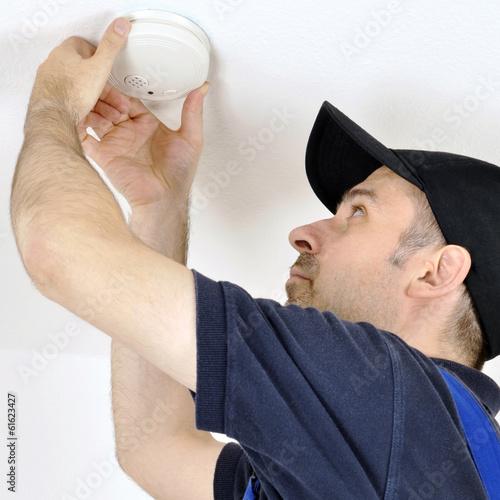 Leinwanddruck Bild Handwerker montiert Rauchmelder als Feueralarm