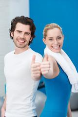 zufriedenes paar im fitness-center zeigt daumen hoch