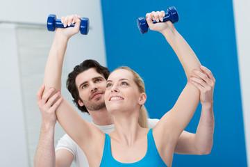 fitness-trainer unterstützt eine kundin