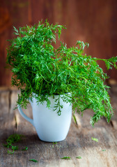 Fresh dill in a glass on a wooden board