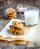 Homemade oatmeal cookies with nuts and raisins and milk with red