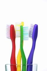 Four Toothbrushes standing in a glass on a white background