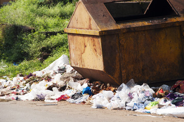 Trash bin with trash around it