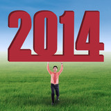 Businessman lifting new year 2014 on the field