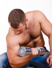 Muscular guy doing exercises with dumbbells on a white