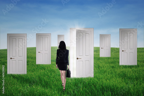Businesswoman walks into opportunity doors
