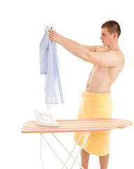 young man in towel ironing shirtl, white background