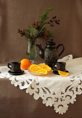 Coffee service, oranges and candy on a white napkin