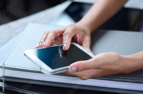 Hands of a businesswoman using a smartphone