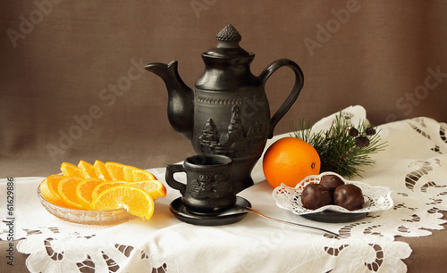 Still life with oranges, sweets and coffee service