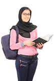 Female Arabic student with backpack holding a book