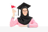 Islamic student with mortarboard and veil holding diploma behind
