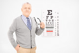 Mature man holding a pair of glasses in front of an eye chart