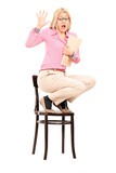 Terrified woman standing on a chair