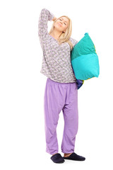 Young woman in pajamas holding a pillow and stretching herself
