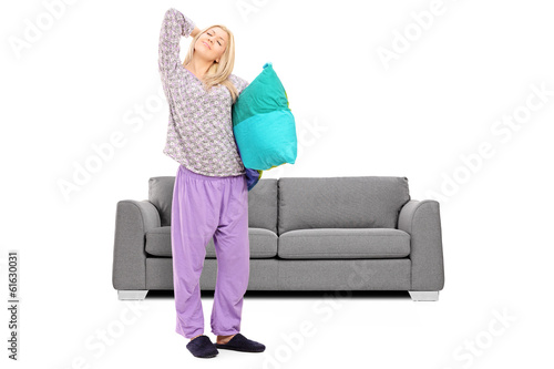 Young woman in pajamas stretching in front of a sofa