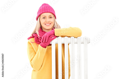 Young woman in winter clothes sitting next to a radiator