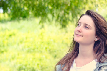 Beautiful young woman daydreaming in a park